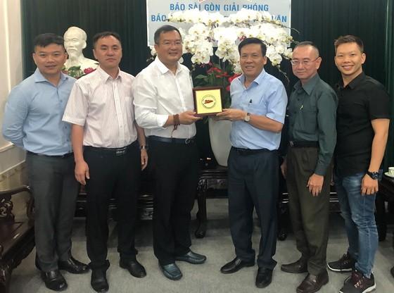 趙騫會長(左三)向本報領導贈送花籃與紀念品。