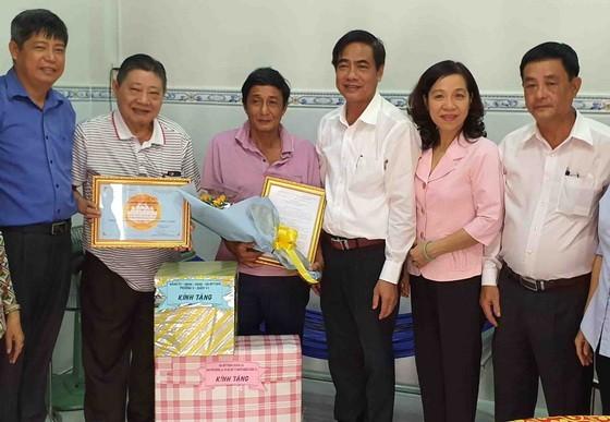杭慰瑤董事長(左二)與吳文論書記(右三) 向貧戶移交溫情屋及春節禮物。
