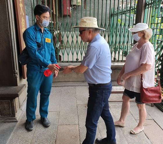 在穗城會館,遊客及善信進廟前先噴抗菌洗手液。