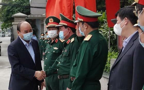 阮春福總理出席會議前與國防部領導握手。(圖源:黃陲)
