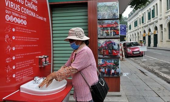 一名女士在李太祖塑像區域附近的洗手站洗手。