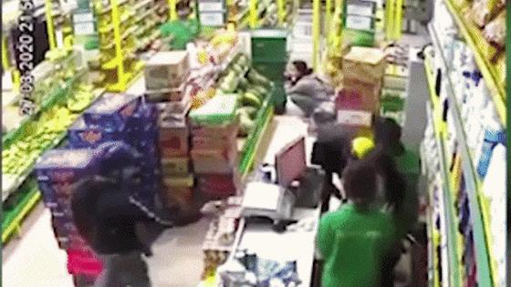 一名手持著疑似手槍的劫匪控制收銀櫃檯員被監控器錄取的畫面。(圖源:視頻截圖)