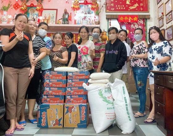 梁柳嬋(右一)與員工準備將大米和麵發送給窮人。