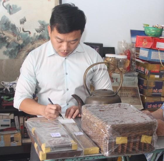 """作者在整理陶女士捐贈""""西堤華人文化陳列室""""的文物。"""