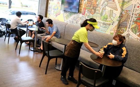 第一郡阮秉謙街某咖啡廳只接待最多20名食客,同時確保桌椅 距離安全。