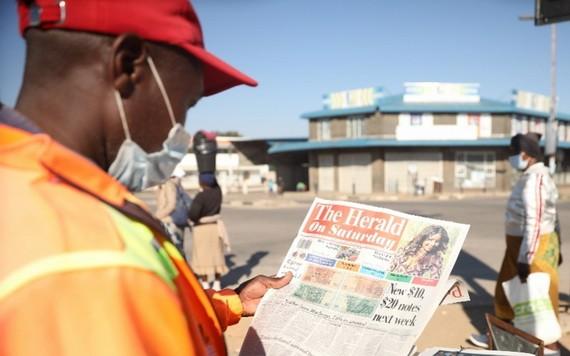 5月16日,在津巴布韋首都哈拉雷,市民瀏覽刊登10元和20元面值的新津巴布韋元票樣的報紙。(圖源:新華社)