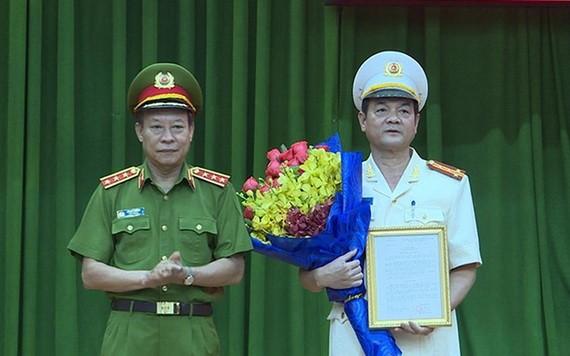 公安部副部長黎貴王向黎鴻南大校(右)頒發人事委任《決定》並送祝賀鮮花。(圖源:H.T)