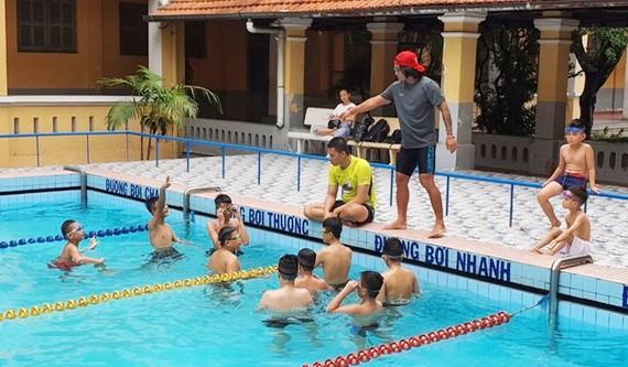 運動員梁玉維正在教孤兒學游泳。