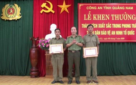 廣南省公安廳代表(中)向 2名取得出色成績的民兵隊員頒授獎狀。(圖源:明俊)