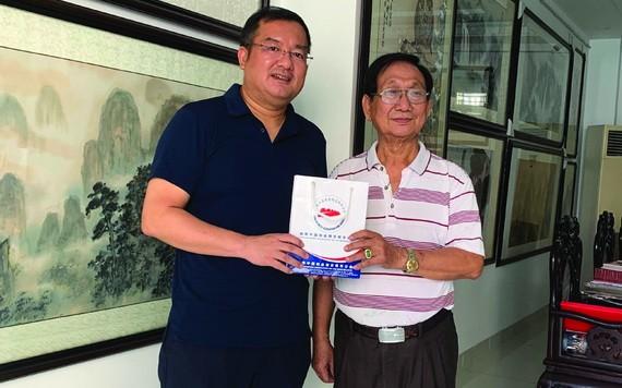 趙騫會長(左)向張漢明畫家贈送禮物。