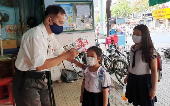 禮文華文中心老師在校門前給學生測量體溫。