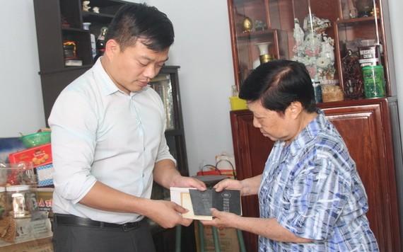 """芳泉鹿嘜汽水廠後人陶妙萍(右)向陳列室捐贈其先父母與她的""""華僑登記證""""。"""