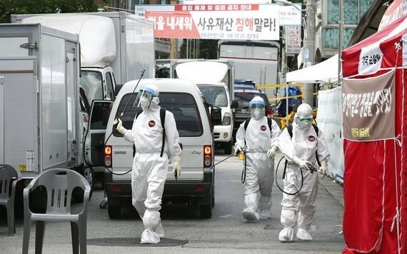 公共衛生職員在首爾一個「愛第一」教會址附近進行消毒。(圖源:AP)