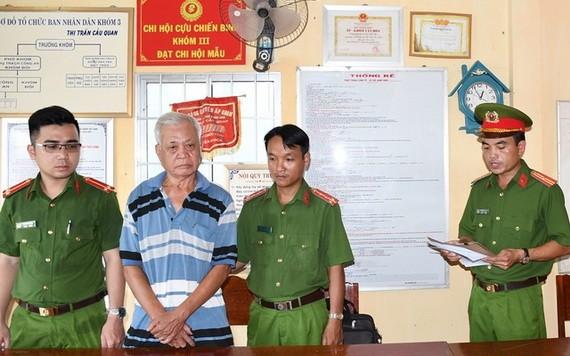涉案嫌犯陳金利(左二)站立著聽取執法警員宣讀拘捕令。