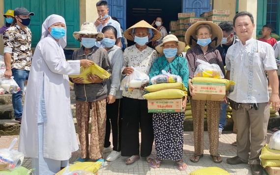 鄒國榮(右一)向貧困者派發禮物。