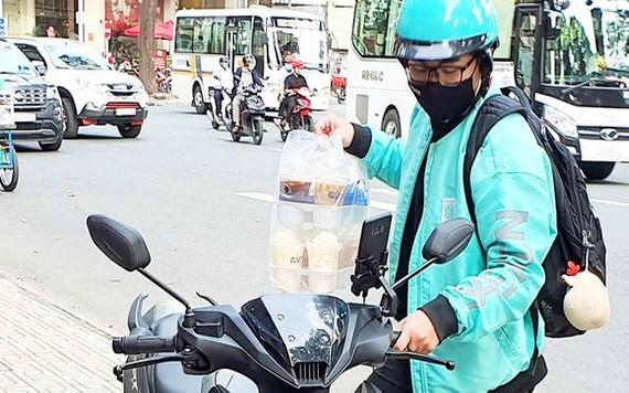 送貨員送一次性塑料杯裝的咖啡。
