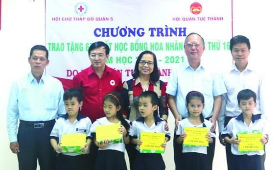 盧耀南理事長(右二)與本市、第五郡領導向五胞胎兄弟姐妹頒發獎學金。