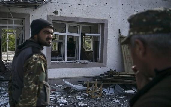 圖為亞美尼亞士兵站在被部分摧毀的軍事醫院建筑前。(圖源:AFP)