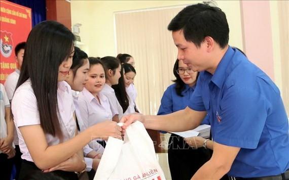 共青團廣平省省委代表向家境貧困的老撾大學生贈送禮物。(圖源:越通社)