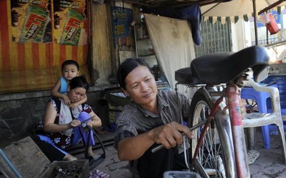 何文鴻正在修車謀生。