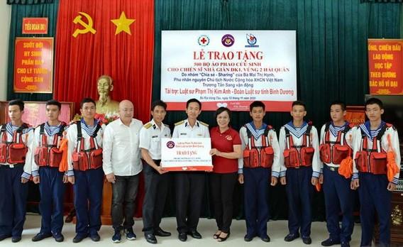 原國家主席張晉創夫人梅氏幸(右五)向DK1瞭望台營的幹部戰士們贈送救生衣。(圖源:春強)