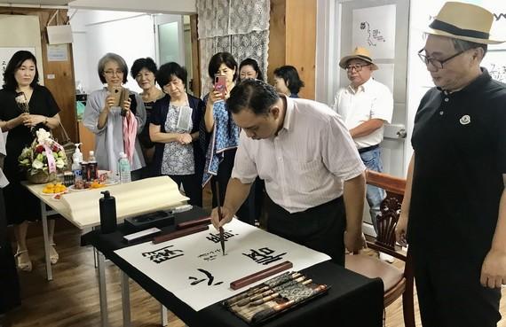 韓國書法愛好者觀賞林漢城即席揮毫。