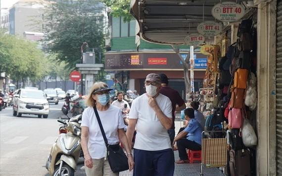 兩名外籍遊客佩戴口罩遊逛市中心街道。(圖源:清真)