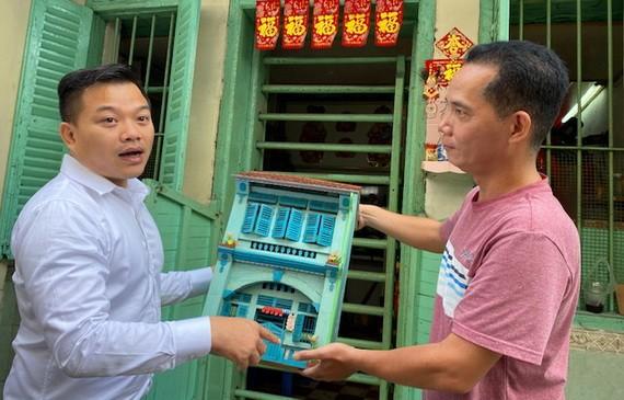 """鄧栢沂(右)把老房子的模型捐贈給""""西堤華人文化陳列室""""計劃。"""