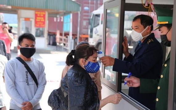 從老撾回國的越南公民入鏡時接受體溫測量。(圖源:Zing)