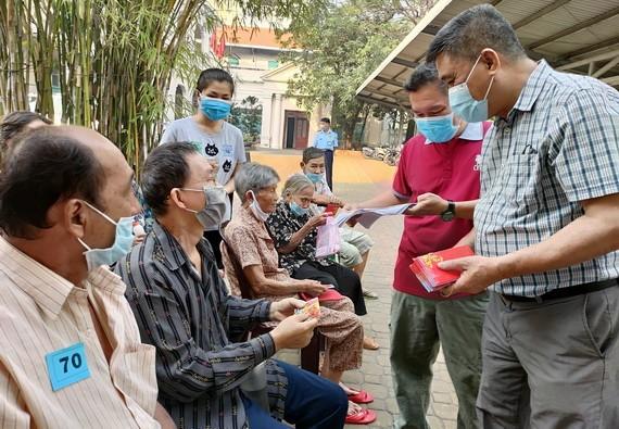 梁栢滔先生向華人貧病者贈送紅包。