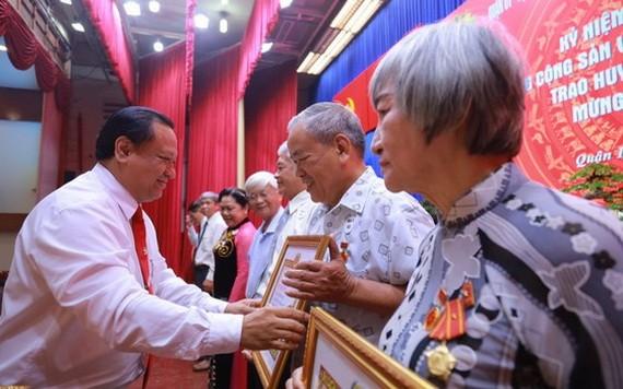 第十一郡郡委副書記陳飛龍(左)向各位高齡黨員頒授黨齡紀念章。(圖源:愛真)