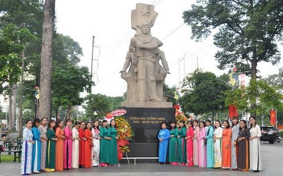 民族婦女工作組的成員穿長衫在第五郡民軍紀念台前合影。