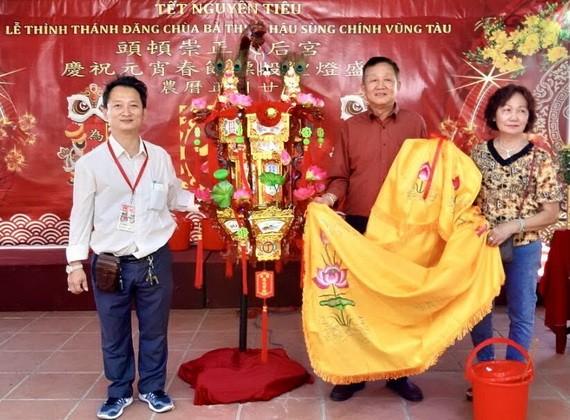 理事長鄒國榮(左)向陸國明夫婦轉交投得的《觀音蓮花寶燈》。