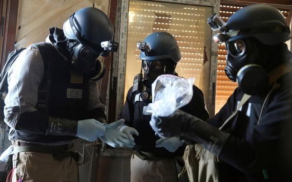 敘利亞危機爆發以來,敘境內的杜馬鎮、薩拉基卜市等多個地點據稱曾發生化武襲擊事件。戴著防毒面具的聯合國化學武器專家檢測一個裝有生化學武器襲擊的樣品。 (圖源:路透社)