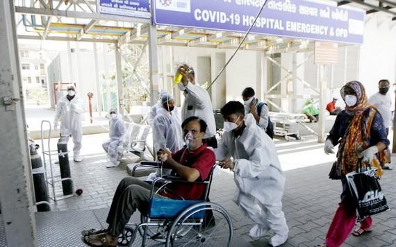 5月3日,醫務人員在印度艾哈邁達巴德的醫院內幫助新冠患者。(圖源:新華社)