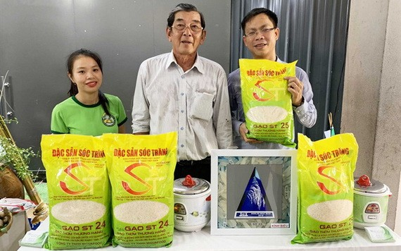 ST25大米品牌研發人胡光郭(中)與推銷員在推介ST25大米品牌。(圖源:H.Đ)
