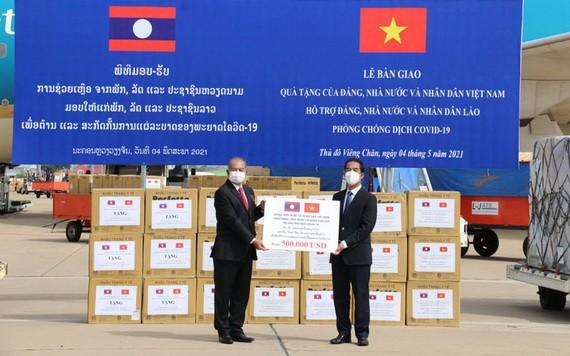 外交部副部长苏英勇(右)在老挝万象瓦岱国际机场向老挝副总理吉乔·凯坎匹吞转交捐赠医疗物资并象征性为老挝新冠肺炎疫情防控工作捐助50万美元。(图源:春山)