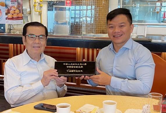 """吳清華先生(左)把中國銀行贈予他的紀念幣轉送給""""西堤華人文化陳列室""""計劃。"""