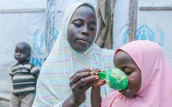 加利福尼亞州的一位母親用從世界糧食計劃署處的糧食點領取的穀類食品為她的孩子準備食物。(圖源:聯合國)