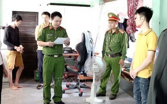 涉賭嫌犯(黃衣)在聽取執法警員宣讀逮捕令。(圖源:越通社)