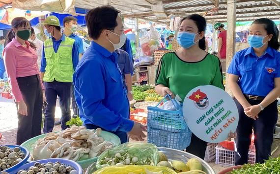 胡志明共青團中央第一書記阮英俊(前左)向民眾宣傳使用環保產品。(圖源:越通社)