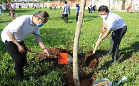 市委原書記阮善仁(左)與平新郡郡委書記黎文聲一同在平治東B坊25號街的公園參加植樹活動。(圖源:喬峰)