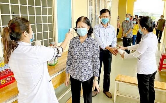 在參加接觸國會代表候選人會議前,古芝縣選民獲量體溫,用殺菌液洗手。