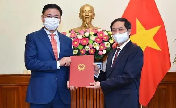 新任外交部副部長范光效(左)從外交部長裴青山手中接過人事委任《決定》。(圖源:國際報)