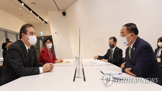 5月25日,在首爾東大門設計廣場舉行的全球綠色目標夥伴2030峰會(P4G)綠色新政特別會議上,南韓副總理兼企劃財政部長官洪楠基(右)和聯合國綠色氣候基金執行董事雅尼克·格萊馬雷克會面。(圖源:韓聯社)