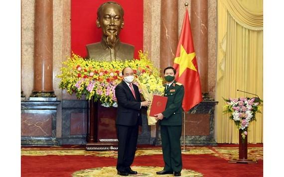國家主席阮春福(左)向阮新剛上將頒授委任《決定》。(圖源:玉興)
