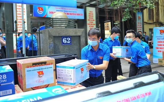 胡志明共青團中央幹部搬運貨物捐助疫區。(圖源:越通社)