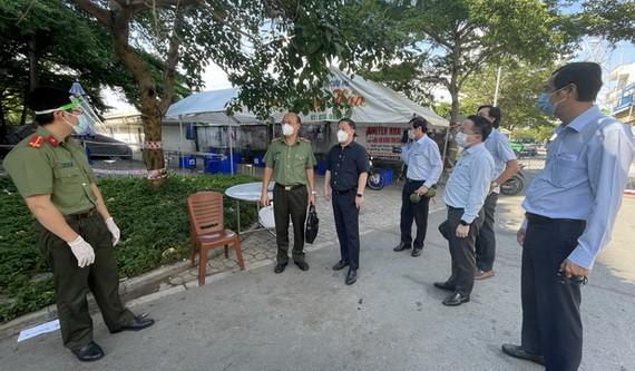 市人委會副主席楊英德(中)同工作團突擊檢查平新郡一隔離區的疫情防控工作。(圖源:文明)