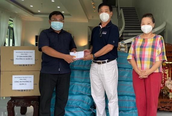 華人熱心人士鄧栢榮、區美莉伉儷(右)向第十一郡第一坊領導移交支持防疫物資。