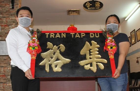 趣兒記者(右)把木雕老招牌捐贈給陳列室。